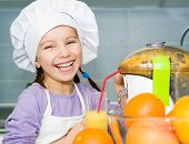 girl  making orange juice with a juice extractor