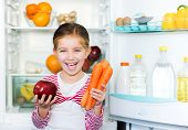 girl with carrots on background refrigerator