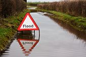 stock photo of flood  - Flood warning sign on a flooded country road - JPG