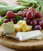 Cheeseboard with three kinds of cheese and grapes