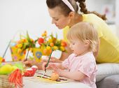 stock photo of mummy  - Mother and baby girl making Easter decorations