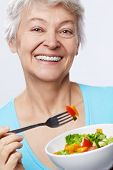 Elderly woman eating salad on white background