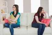 Two friends not talking to each other after fight on the sofa in sitting room at home