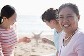 Portrait of multi- generational family on the beach, starfish