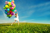 Happy birthday woman against the sky with rainbow-colored air balloons in hands. sunny and positive energy of nature. Young beautiful girl on the grass in the park.