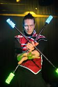 Performance of a man with tattoo and terrible pupils in samurai garb with glow sticks, sticks crossed in front of him.