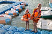Mother and daughter on the dock with round inflatable boats with electric motor