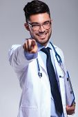 young male doctor pointing and looking at the camera with a clipboart in his hand and a smile on his face. on gray background