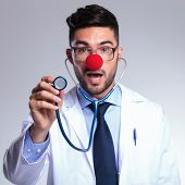 young male doctor listening at stethoscope while wearing a clown red nose and looking into the camera with his mouth opened. on gray background