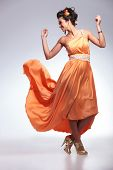 full length picture of a young fashion woman with her dress flying in the air while she dances and looks away with her hands up. on gray background