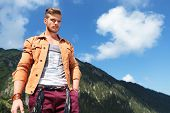 young casual man posing outdoor in the mountains, looking down into the camera while holding a hand into his pocket
