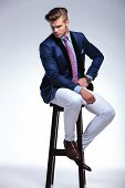 full length picture of a young business man sitting on a chair and looking down while holding a hand on his hip. on a gray background