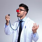 young male doctor listening himself sing at the stethoscope while wearing a clown red nose. on gray background