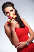 young beauty woman smelling some roses while looking into the camera. on gray background