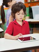 Little boy using digital at desk with friend in background at kindergarten