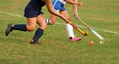 Two women battle for control of ball during field hockey game