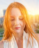 Redhead backlit by the sun closed eyes