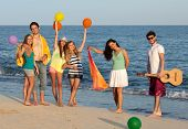 Group Of Young People Enjoying Beach Party With Guitar And Balloons