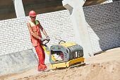 image of vibration plate  - builder worker compacting soil with vibration plate compaction machine during pavement roadwork - JPG