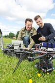 Happy young male technicians discussing over digital tablet by UAV drone in park
