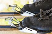 stock photo of ski boots  - Old black leather ski boots in ancient ski clamps - JPG