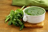 stock photo of green pea  - green cream soup of spinach and green peas in white bowl - JPG