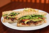 stock photo of deli  - A deli classic bacon lettuce and tomato sandwich with avocado on whole wheat bread - JPG