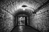 stock photo of fortified wall  - corridor dark dungeon with a dim lamp on the ceiling - JPG