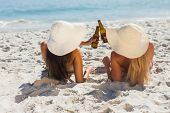 Attractive blonde and brunette with straw hats and bikinis clinking glass bottles
