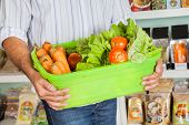 Midsection of mid adult man holding basket of fresh vegetables in supermarket