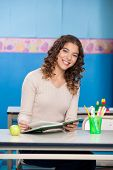 Portrait of young teacher with book sitting at desk in classroom