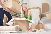 stock photo of independent woman  - Happy young woman unpacking boxes in new home - JPG
