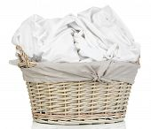 Rumpled bedding sheets in wicker basket isolated on white