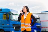 Logistics - female Asian forwarder or supervisor with mobile phone, in front of trucks and trailers,
