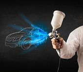 stock photo of gun shop  - Worker with airbrush gun painting hand drawn white car lines - JPG