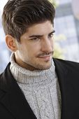 Close-up portrait of casual young man in polo-neck sweater and jacket, looking away.