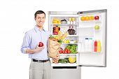 Smiling man holding a paper bag in front of refrigerator full of products and looking at camera, isolated on white background