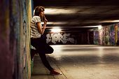 Stylish young girl standing in grunge graffiti tunnel, shanty town. Fashion, trends, subculture. Ful