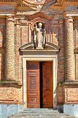Facade of red brick catholic church with old ornate wooden doors in town of La Morra in Piedmont, Norther Italy.