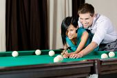 Man teaching girl to play billiards. Spending free time on gambling