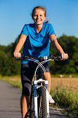 Healthy lifestyle - young woman biking