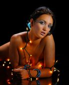 foto of implied nudity  - Nude woman wearing Christmas lights on black background - JPG