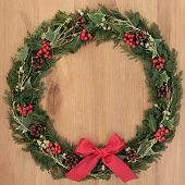 Christmas wreath with red bow decoration, holly, mistletoe and winter greenery over oak background.