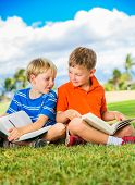 Happy Kids, Young Boys Reading Books Outside Together after School