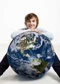 Young man resting over a small planet earth - Image of planet provided by Nasa
