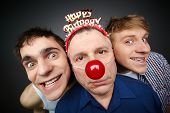 Two guys having fun playing pranks on a senior man celebrating birthday or fool�?�¢??s day