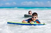 Mother and son surfing on boogie boards
