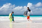 image of boogie board  - Father and son running towards ocean with boogie boards - JPG