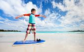 Little boy on vacation having fun learning surfing at beach