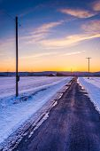 Sunset Over A Country Road Through Snow Covered Fields In Rural Frederick County, Maryland.